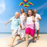 Familie, die mit Drachen auf Strand läuft lizenzfreie stockfotos