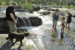 Familie, die mit einem Hund spielt Lizenzfreie Stockfotografie