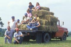 Familie, die mit Heuballen auf LKW sitzt Stockfoto