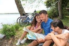 Familie, die mit Karte sitzt Lizenzfreies Stockfoto