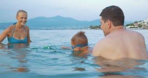 Familie, die mit Spielzeugfrosch im Meer spielt stock footage