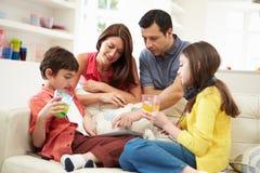 Familie, die mit Tablet und MP3 spielt Stockbild