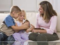 Familie, die mit Welpen spielt Stockbild