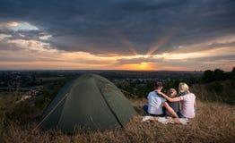 Familie, die nahe Lagerzelt auf dem Hügel sitzt stockfotografie