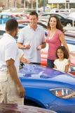 Familie, die neues Auto mit Verkäufer behandelt Stockbilder