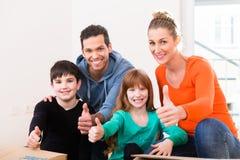 Familie, die in neues Haus oder in Haus sich bewegt Lizenzfreies Stockfoto