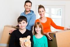 Familie, die in neues Haus sich bewegt Stockbilder