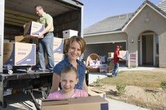 Familie, die in neues Haus sich bewegt Stockfotos