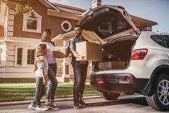 Familie, die in neues Haus sich bewegt lizenzfreies stockbild