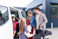 Familie, die Neuwagen im Auto-Vertragshändler überprüft Stockfotografie