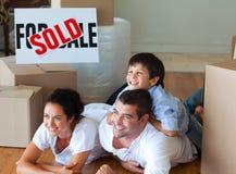 Familie die nieuw huis het liggen op vloer koopt Stock Fotografie
