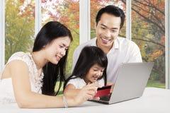 Familie die online thuis met de herfstachtergrond winkelen stock fotografie