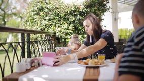 Familie die ontbijt hebben bij openluchtkoffie Aanbiddelijk meisje en mamma die vers sap drinken en croissant op terras eten stock footage
