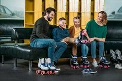 familie die op bank rusten alvorens in rolschaatsen te schaatsen stock afbeeldingen