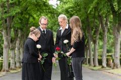 Familie die op begrafenis bij begraafplaats rouwen Stock Afbeeldingen