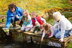 Familie die op Brug in Vijver met Netto vissen royalty-vrije stock foto