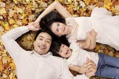 Familie die op de herfstbladeren liggen Stock Foto