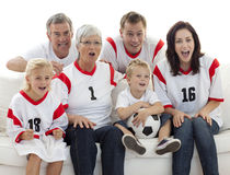 Familie die op een voetbalgelijke in televisie let stock afbeelding