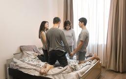 Familie die op het bed thuis op het begin van de dag bidden stock afbeeldingen