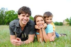 Familie die op het groene gras ligt Stock Foto