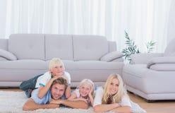 Familie die op het tapijt liggen Stock Afbeeldingen