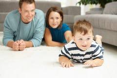 Familie die op tapijt ligt royalty-vrije stock fotografie
