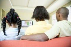 Familie die op TV let Stock Foto