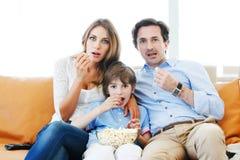 Familie die op TV let Stock Afbeeldingen