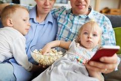 Familie die op TV letten en popcorn eten royalty-vrije stock foto
