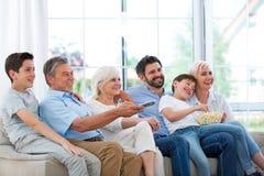 Familie die op TV op bank letten Royalty-vrije Stock Foto's