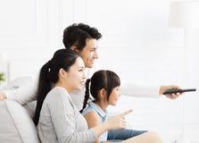 Familie die op TV in woonkamer letten royalty-vrije stock afbeeldingen