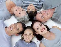 Familie die op vloer met hoofden samen ligt Stock Fotografie