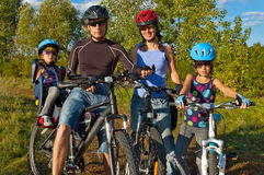 Familie die in openlucht cirkelt. Ouders met jonge geitjes op fiets Stock Foto's