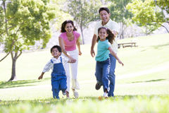 Familie die in openlucht het houden van handen en het glimlachen in werking stelt Stock Fotografie