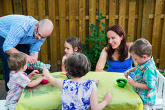 Familie, die Ostereier malt Stockbild