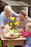 Familie die Paaseieren op Lijst in openlucht verfraait Royalty-vrije Stock Afbeelding