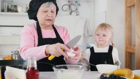 Familie die pannekoeken maken Een oude vrouw voegt eieren in het deeg toe stock videobeelden