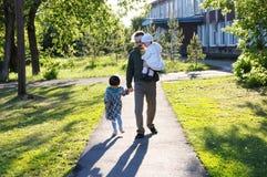 Familie die in Park lopen vader met dochters bij zonnige dag papa en meisjes die verhouding plakken stock afbeelding