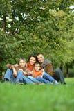 Familie die in park rusten Stock Afbeelding