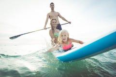 Familie die peddelbranding in de oceaan maken Stock Foto