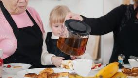 Familie, die Pfannkuchen isst und Tee trinkt Früchte auf der Tabelle stock video