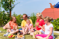 Familie, die Picknick in der Gartenfront ihres Hauses hat Stockbilder