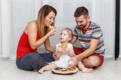 Familie, die Pizza isst Vater, Mutter und Tochter zu Hause stockfotos