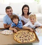 Familie die pizza op bank eet royalty-vrije stock foto's