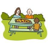 Familie, die Pizza am Picknicktisch isst Stockfotos