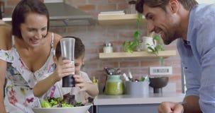 Familie die plantaardige salade in keuken voorbereiden bij comfortabel huis 4k stock videobeelden