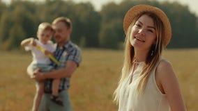 Familie die pret in aard hebben Het jonge vrouw stellen voor de camera Mens en kind het spelen op de achtergrond stock footage