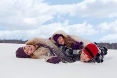 Familie die pret in de sneeuw heeft Stock Afbeeldingen