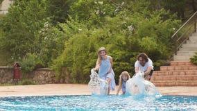 Familie die pret hebben hun pool dient het familie bespattende water met benen of zwembad in stock video