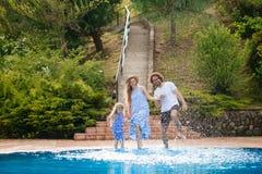 Familie die pret hebben hun pool dient het familie bespattende water met benen of zwembad in stock afbeelding